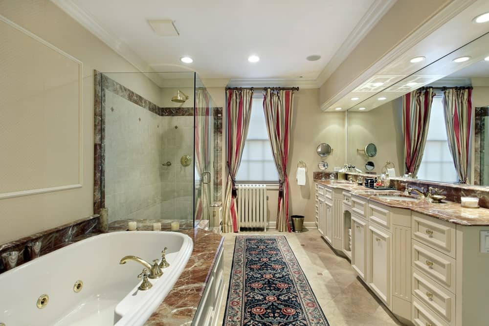 Red striped curtains and a lovely floral runner stands out in this beige primary bathroom with a drop-in tub and dual sink vanity topped with elegant marble counter.