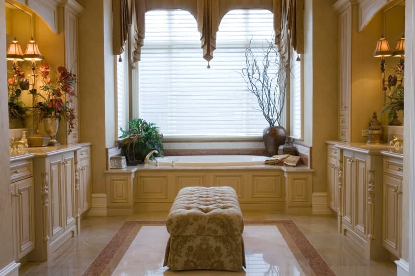 This primary bathroom showcases facing vanities with tufted ottoman in the middle over marble flooring. It includes a drop-in tub by the glazed window dressed in charming valances.