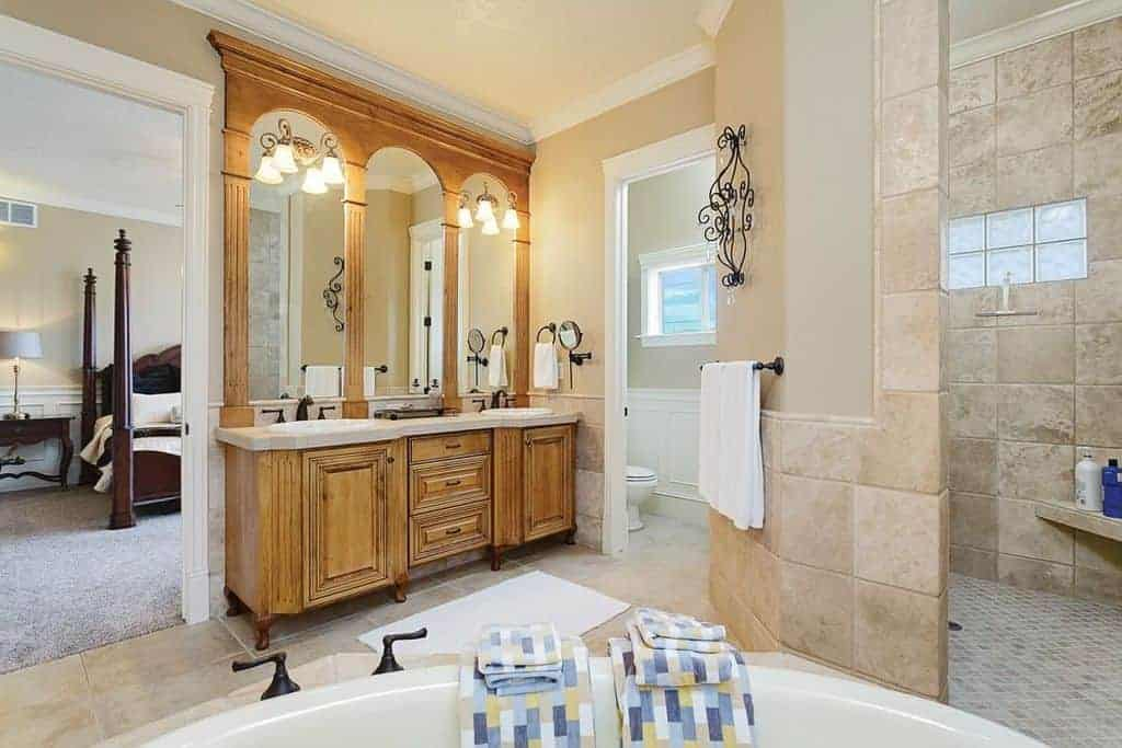 Bright primary bathroom completed with a shower and toilet area along with a deep soaking tub that faces the wooden sink vanity fitted with wrought iron fixtures.