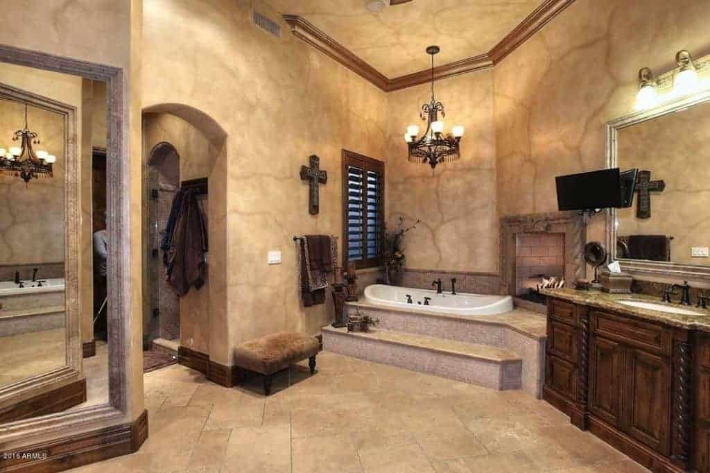 Mediterranean primary bathroom with sink vanity and a brick fireplace fixed above the drop-in bathtub. It is lighted by a vintage chandelier that hung from the regular ceiling lined with wooden <a class=