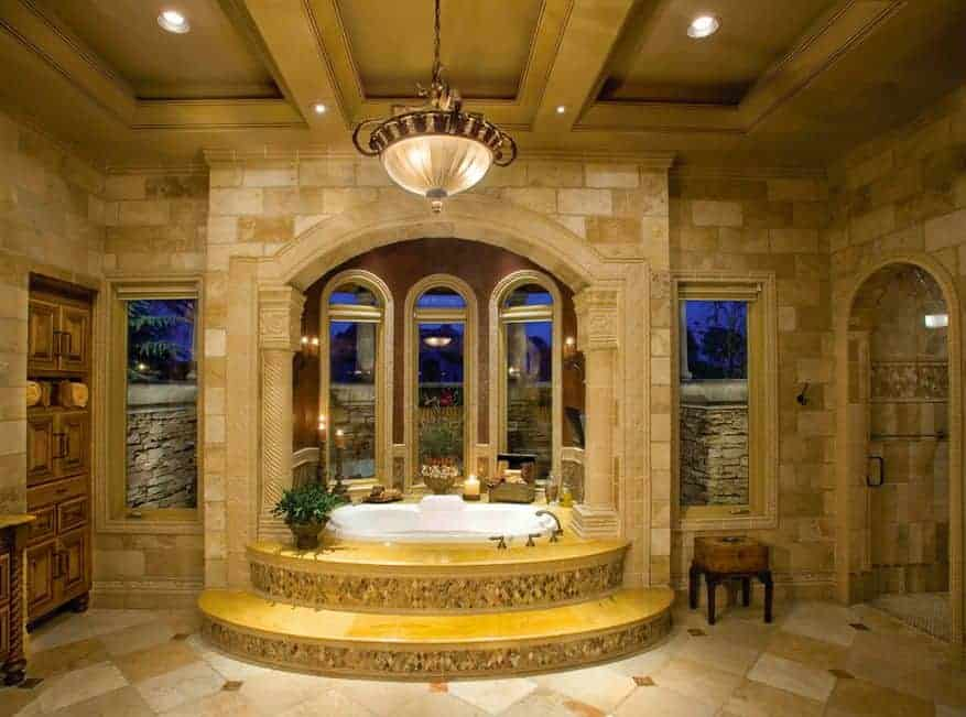 A small cushioned chair sits in between the walk-in shower and alcove bathtub that's illuminated by a dome chandelier and recessed ceiling lights.