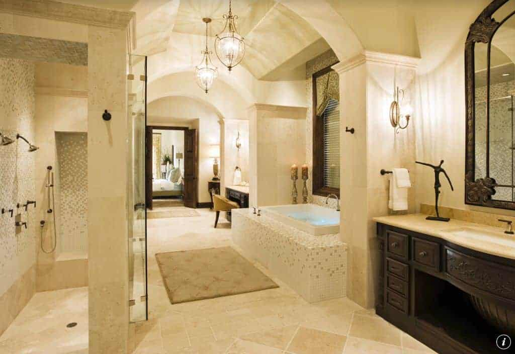 Well-lit primary bathroom boasts carved wood vanities with a deep soaking tub in the middle that's clad in mosaic tiles matching with the walk-in shower's walls.