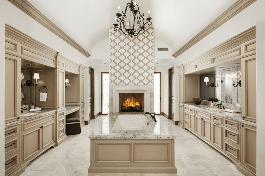 An ornate candle chandelier hangs over the drop-in tub attached to the patterned pillar that's fitted with a fireplace. It is flanked by built-in vanities with wrought iron hardware.