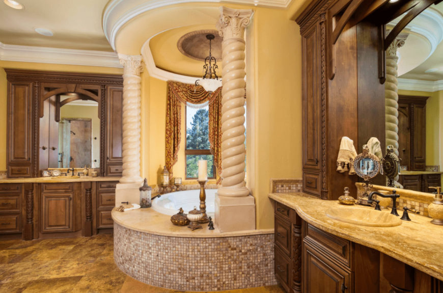 Classy primary bathroom with alcove tub and wooden sink vanities topped with limestone counters that complement the tiled flooring.