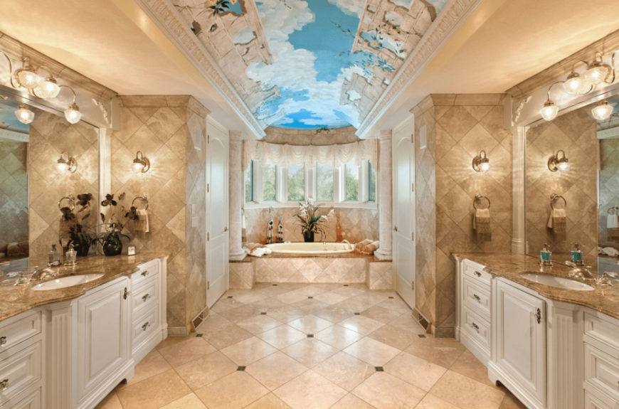 Mediterranean primary bathroom with a stunning sky ceiling and marble tiled flooring arranged in a diamond pattern. It includes facing white sink vanities topped with frameless mirrors.