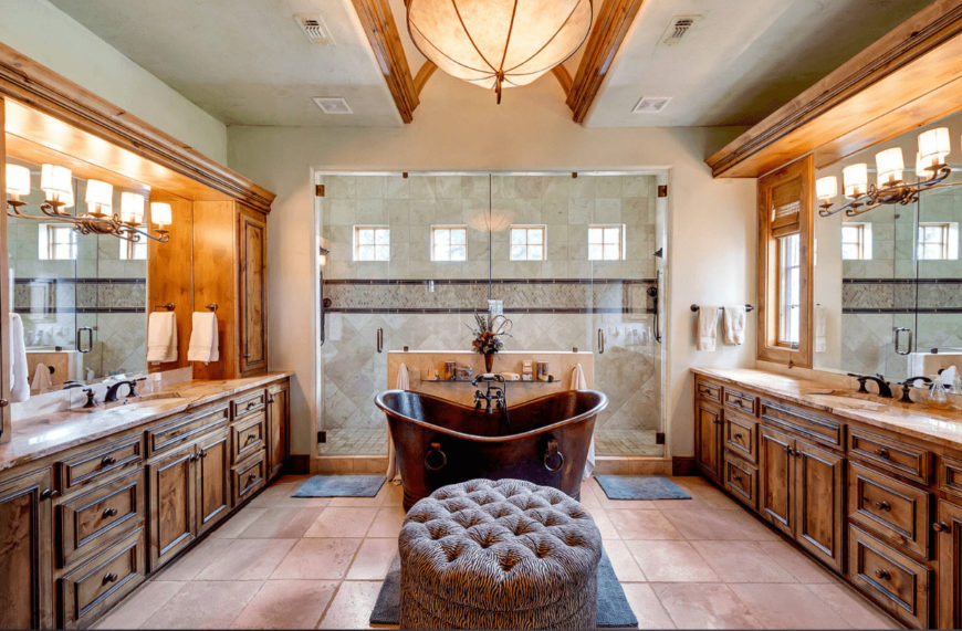 The beige primary bathroom features his and her sink vanity along with a walk-in shower and copper freestanding tub accompanied by a round tufted ottoman.