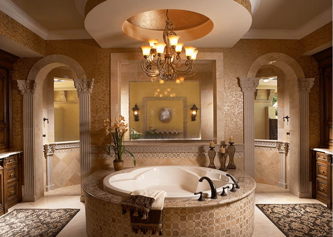 Elegant primary bathroom with a round bathtub illuminated by an ornate chandelier that hung from the tray ceiling. It includes classy rugs and arched doors leading to the walk-in shower.