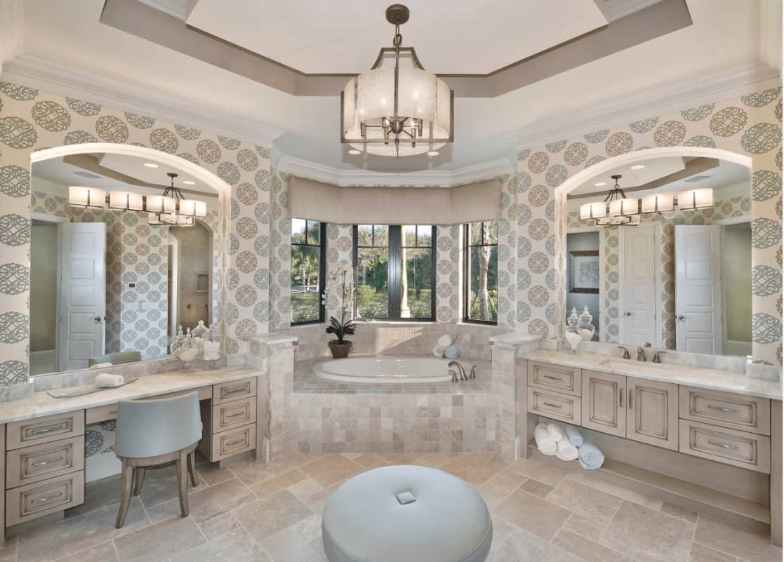 Clad in beige patterned wallpaper, this primary bathroom boasts light wood vanities and a deep soaking tub by the bay window overlooking the lush greenery.
