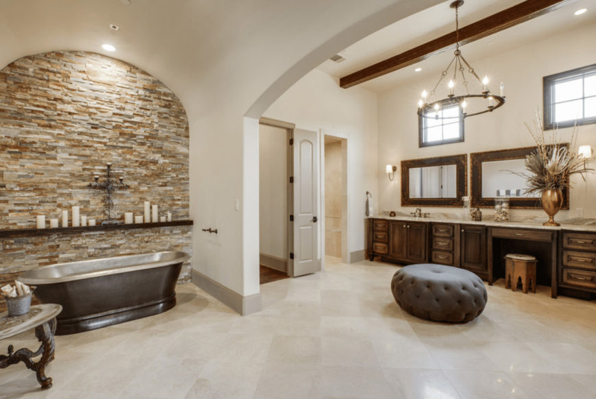 Spacious primary bathroom offers a freestanding bathtub and wooden sink vanity accompanied by a gray tufted ottoman that's lighted by a round candle chandelier.