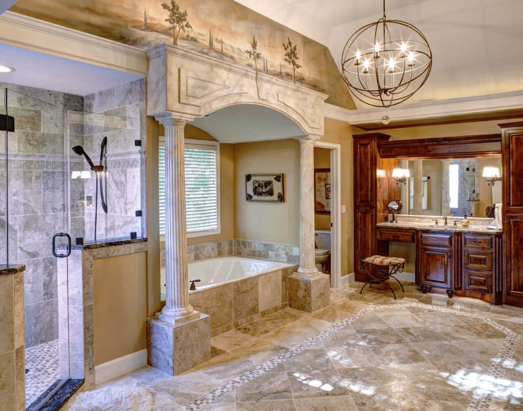 A spherical chandelier illuminates this primary bathroom boasting a wooden sink vanity and alcove tub designed with landscape mural on top.