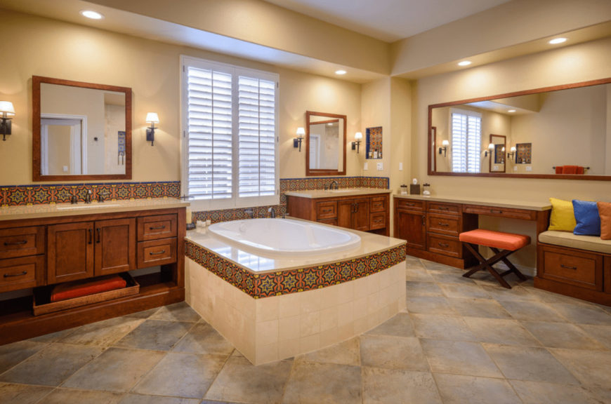 The Mediterranean primary bathroom features a deep soaking tub and wooden vanities lined with eye-catching decorative tiles. There's a built-in seat on the side topped with beige cushion and multi-colored pillows.