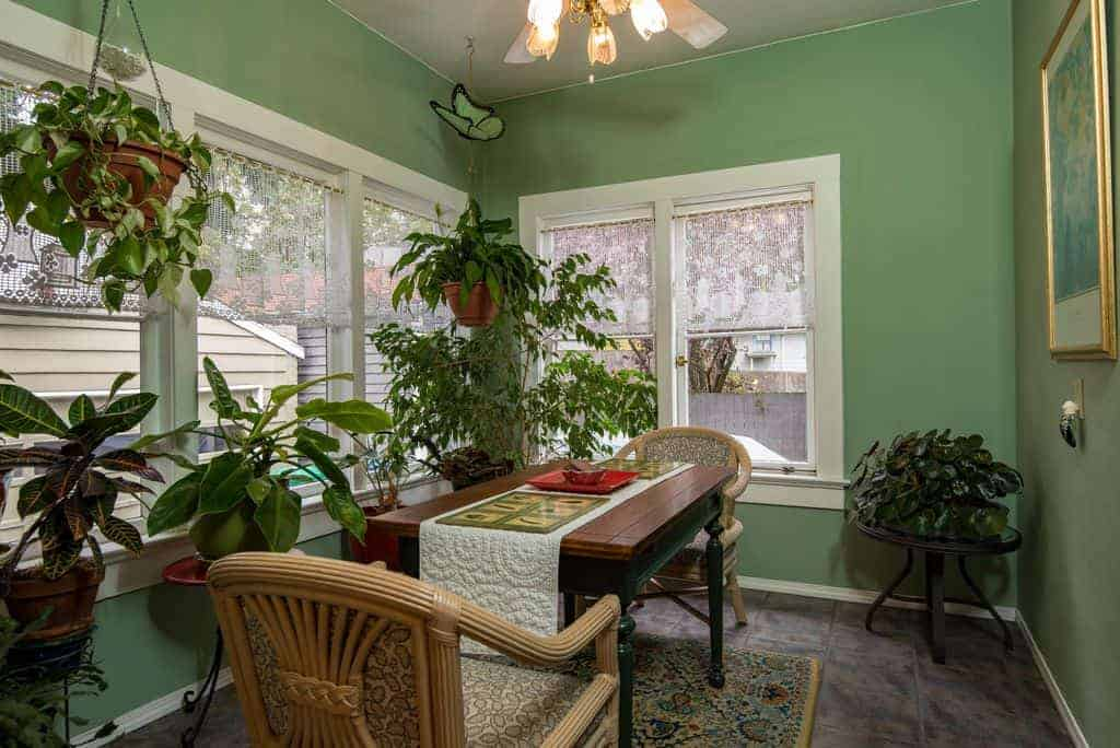 The various potted plants that dominated this Tropical-style dining room is complemented by the green walls brightened by the white frames of the windows that bring in natural lighting for the simple wooden dining table and its two bamboo armchairs that stand out against the gray flooring.