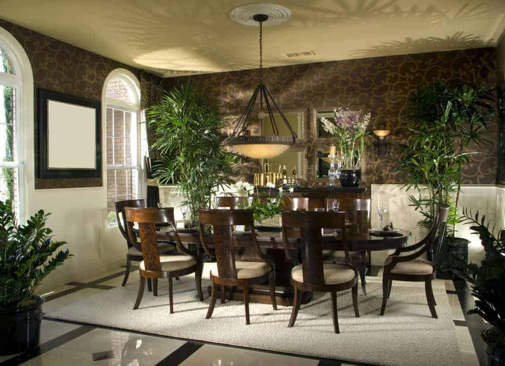 This elegant Tropical-style dining room has white wooden wainscoting that is contrasted by the surrounding potted plants and the brown patterned wallpaper that matches the dark brown hues of the wooden dining table and the surrounding chairs topped with a dark brown dome pendant light.
