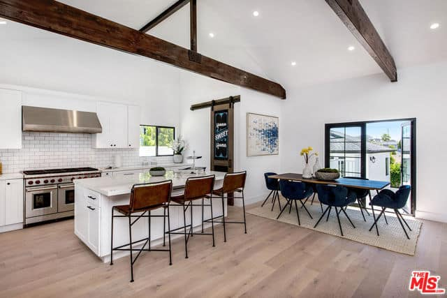 Open space featuring the kitchen and dining area under a pitched ceiling with recessed lighting and wood beams