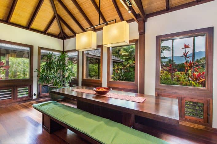 The highlight of this Tropical-style dining room is the lush green scenery of the landscaping outside that is featured by the surrounding windows. These windows have wooden frames that match the hardwood flooring, dining table and its wooden benches with green cushions on them.