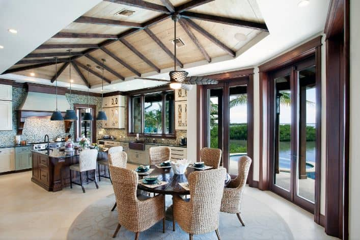 This informal dining room is in the same large room as the kitchen. They are both under a wooden cathedral ceiling with exposed beams supporting a ceiling fan with lighting that has a leaf design. This hangs over the round wooden dining table that stands out against its woven wicker chairs and the beige carpeted flooring.