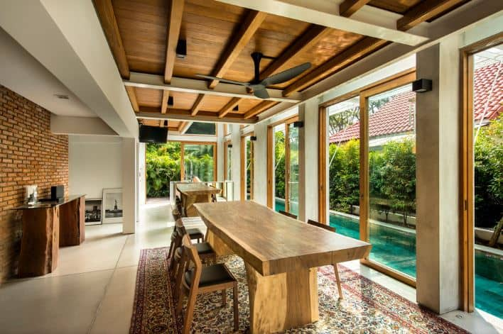 The large white tiles of the flooring is topped with a colorful patterned area rug that gives contrast to the light wooden dining table paired with wooden chairs that have black leather cushioned seats. This setup has a nice view of the blue pool just outside the glass sliding doors.