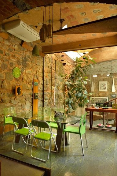 This is a nice fusion of Tropical-style elements and industrial-style elements. It has a tall textured stone wall paired with an arched brick ceiling and a gray concrete flooring. These elements makes the green modern chairs stand out as well as the green wall clock and potted plant.