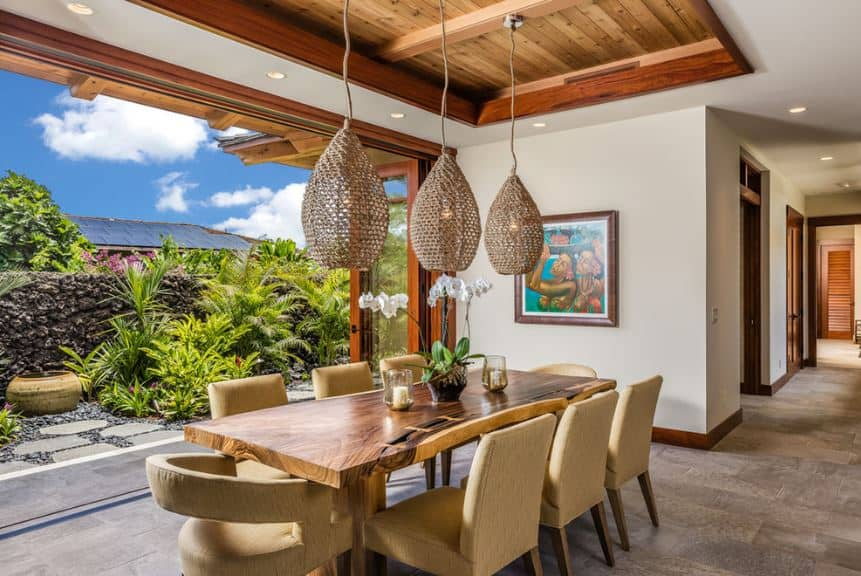 The brown wooden and earthy hues of the ceiling, the basket hoods of the pendant lights as well as the wooden dining set are all given a vibrant background of brilliant green plants of the landscaping just outside of the large wall that opens up with a row of folding glass doors.