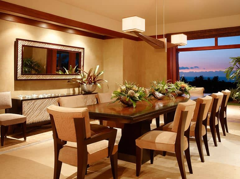 There is a decorative pendant light hanging from the beige ceiling that has two hood lights on each end. The beige ceiling matches the walls that are adorned with a wall-mounted mirror with frames matching the facade of the dining room cabinet below it. They are complemented by the large dining set of wooden table and wooden chairs with beige cushions.