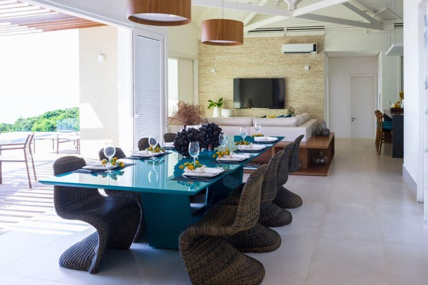 The modern blue rectangular dining table is surrounded by rustic woven wicker chairs that stand out against the white tiles of the floor that is illuminated by the natural lights coming from the large entryway from the yard.