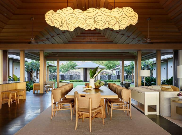 This dining area is in the middle of the living room area and the kitchen with the same arched wooden ceiling and dark hardwood flooring. The highlight of this dining area is the large decorative pendant light that looks like a cartoon cloud.