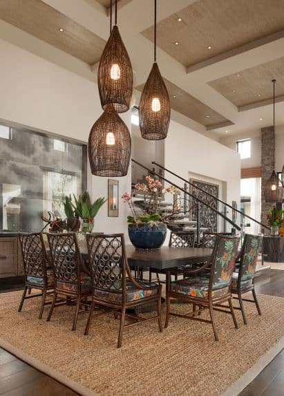 Three pendant lights and their rustic woven wicker hoods pairs well with the brown woven area rug over the dark hardwood flooring. This matches the dark wooden hue of the rectangular dining table and its bamboo chairs with colorful floral cushions.