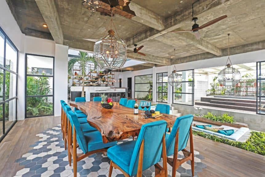 This Tropical-style dining room has an industrial-style concrete gray ceiling with exposed beams supporting the ceiling fans and the large lantern-like pendant light hanging over the large wooden dining table paired with blue velvet chairs with wooden frames.