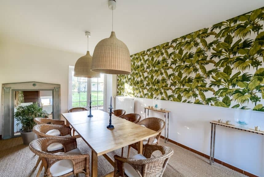 The long rectangular wooden dining table has a light hue to it complemented by the woven wicker armchairs with white seat cushions. These chairs blend with the brown carpeted flooring and the two large rustic basket hood of the pendant lights.