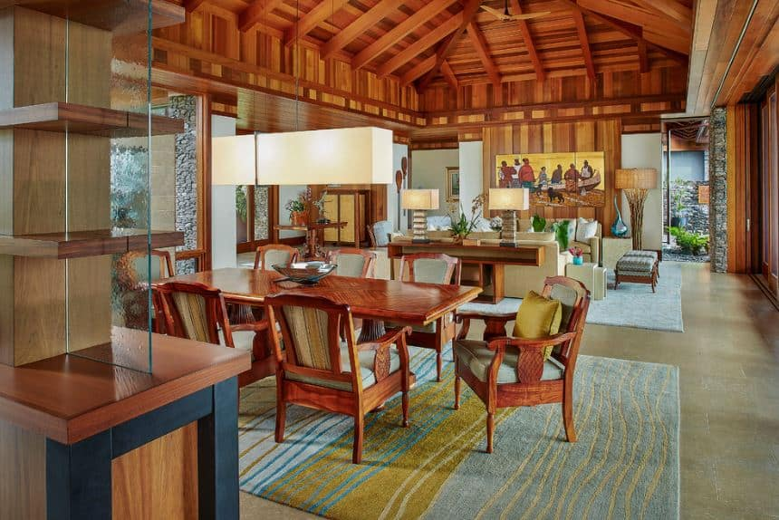 The large wooden cathedral ceiling has wooden exposed beams that support the rectangular pendant light hanging over the redwood dining table and its wooden armchairs with light gray cushions that work well with the blue patterned area rug over the gray flooring.