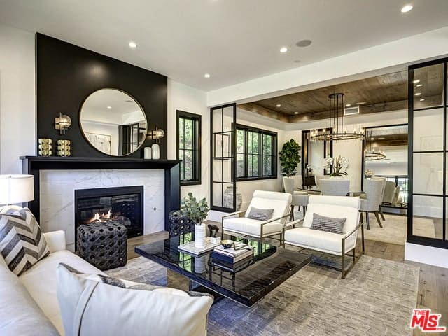 Elegant living room with a round mirror over a marble fireplace, stylish furniture, and a view to the dining room.