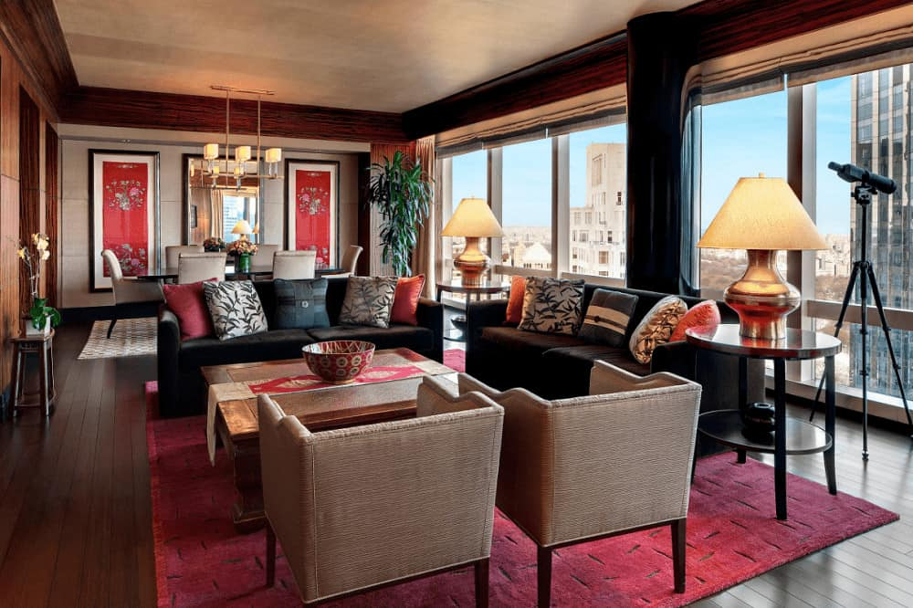 A large living room with multiple seating areas illuminated by stylish table lamps and contemporary chandelier. It has wide plank flooring and panoramic windows framing the city view.