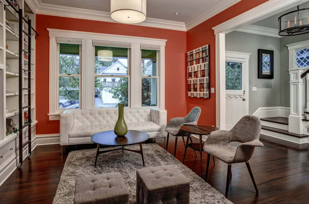 A red living room situated next to the gray foyer featuring cozy seats and a round coffee table topped with a green vase. It includes a drum pendant light and open shelving lined with a black ladder.
