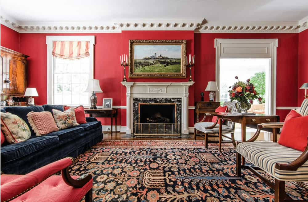 The formal living room features a floral area rug and stunning red walls lined with white crown molding. It has cozy mismatched seats and a fireplace with a framed landscape on top.