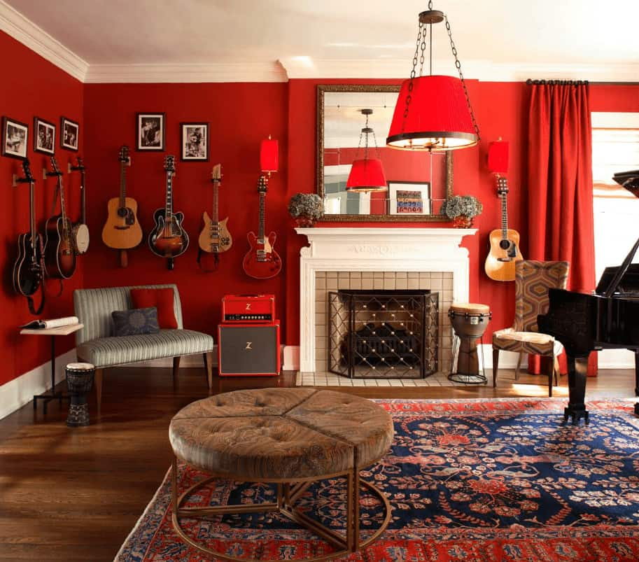 A red living room that doubles as a music room featuring black framed photos and hanging guitars above the green striped seat. It includes round modular ottoman on a classic area rug and a fireplace enclosed in a three-panel screen.