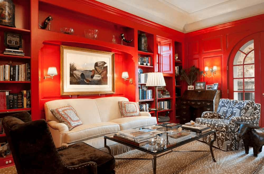 A framed artwork hangs above the beige sofa lighted by sconces and traditional floor lamp. This room has gorgeous seats and built-in shelving filled with books and decors.