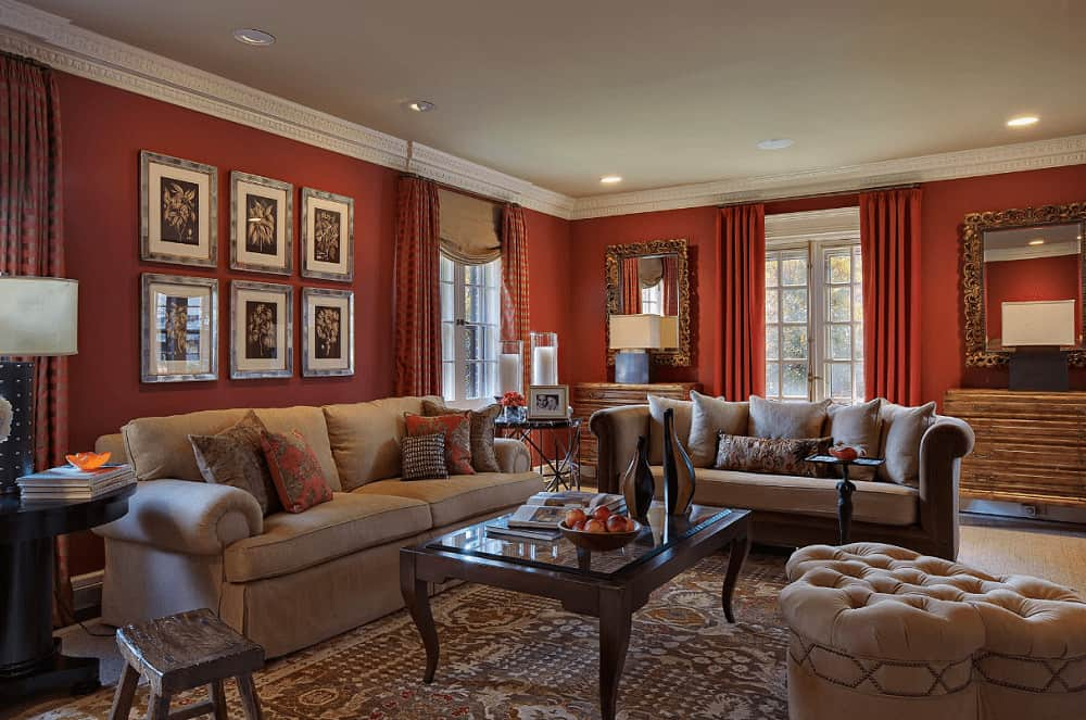 Sophisticated living room decorated with gallery frames and ornate mirrors mounted above the wooden console tables. It has cozy seats and wooden coffee table over a classic area rug.