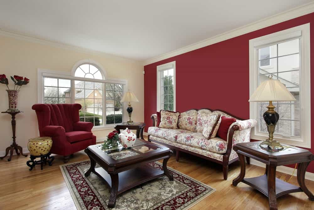 A pleated wingback chair complements the red wall fitted with white framed windows. This room has a floral cushioned sofa and wooden glass top tables over the hardwood flooring.