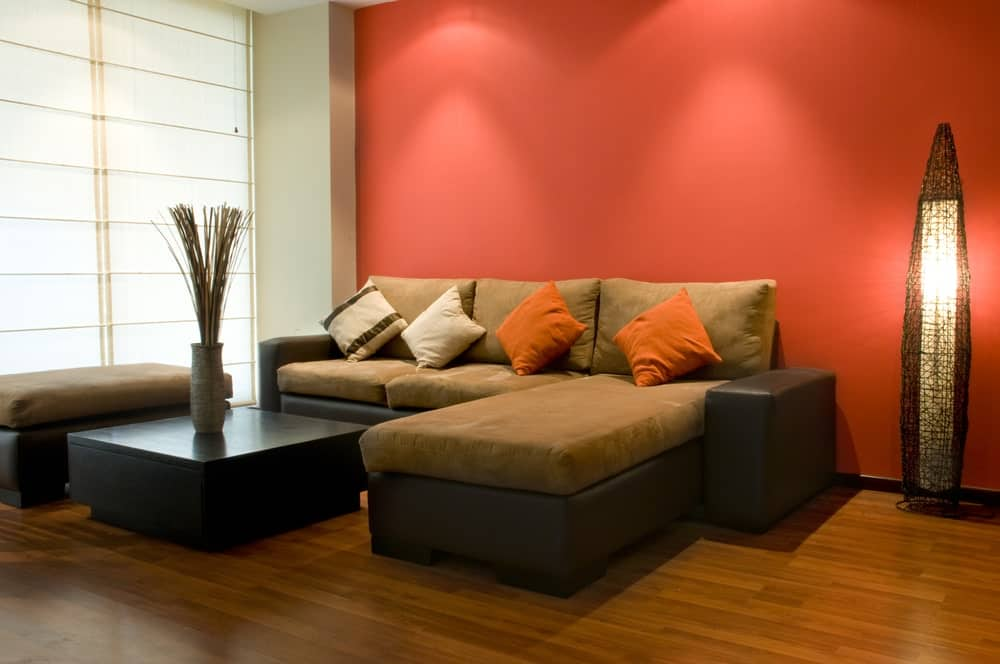 This living room offers a stylish tower lamp and an L-shaped sectional that matches the cushioned ottoman. It includes a black coffee table topped with a flower vase.