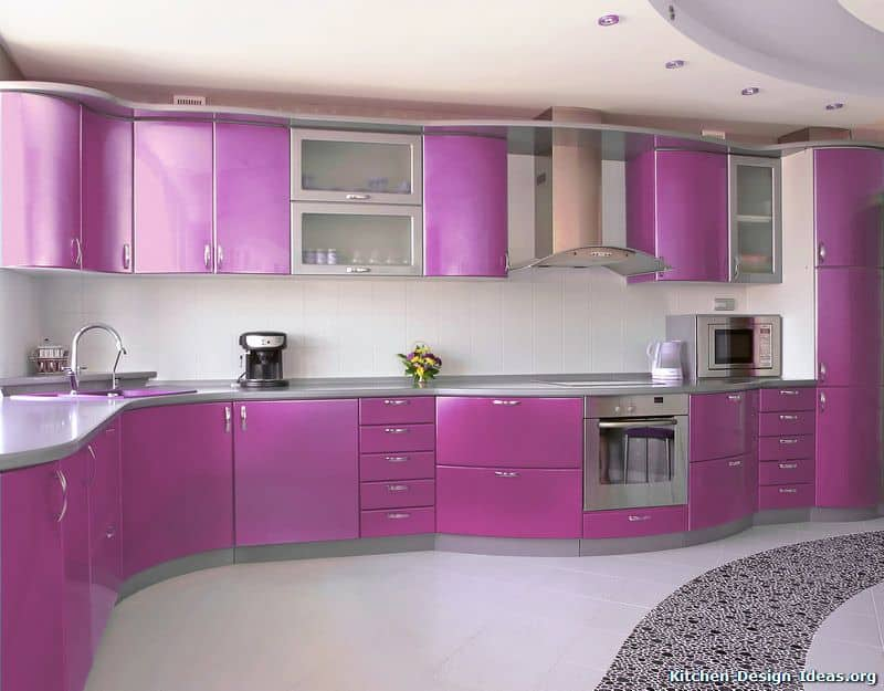 This modern kitchen has a large L-shaped peninsula with a unique curved finish mirrored by the floating cabinet. Both of these have purple cabinets and drawers with silver handles that match the stainless steel appliances.
