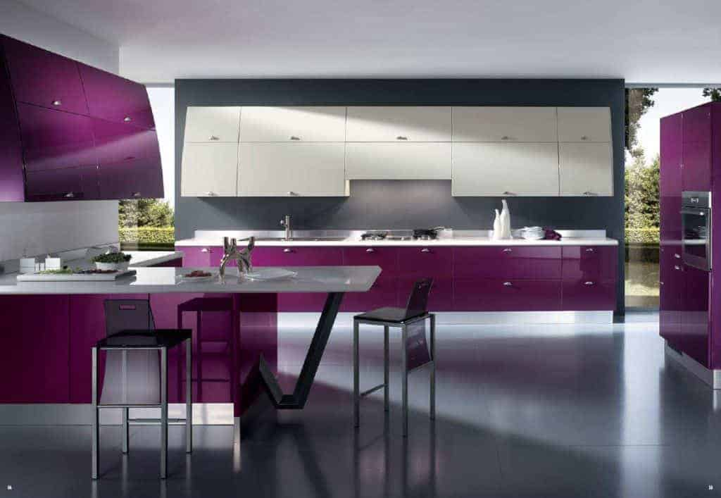 The dark purple hue stands out in this spacious kitchen. It has two peninsulas with the same purple cabinets and drawers. One is against the far gray wall complemented by a row of white floating cabinets above. The other is L-shaped with white countertops that stand out against the gray flooring.