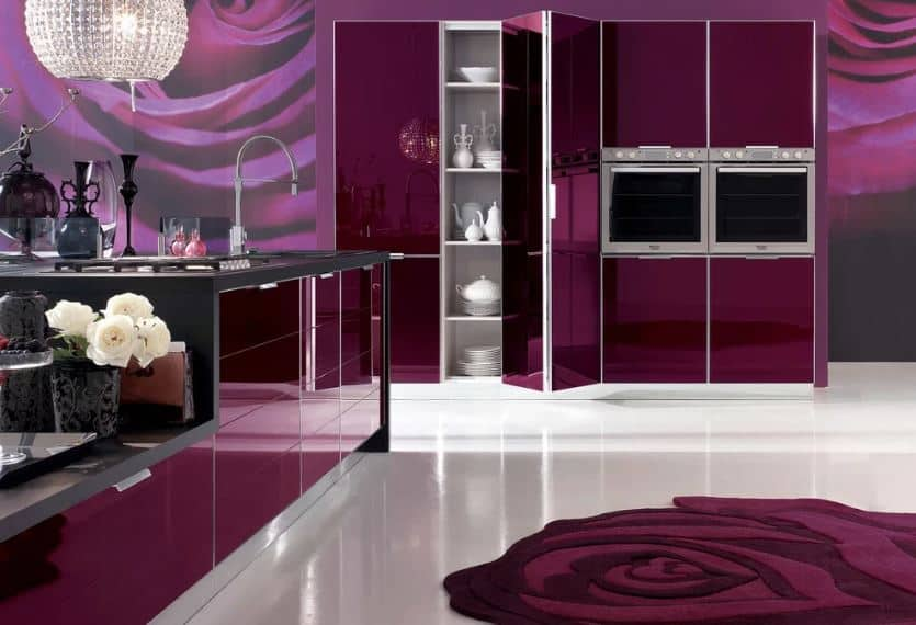 The middle of this modern kitchen's white flooring is adorned with a decorative purple area rug that has a rose design. The purple hue of this area rug matches with the modern cabinetry as well as the wallpaper that has images of a rose in it.