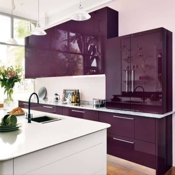 The brightness of this modern kitchen is due to the abundance of natural lights coming in from the tall windows on the side that brightens up the white elements of the kitchen island and ceiling. This is then subdued by the deep purple cabinetry of the peninsula.