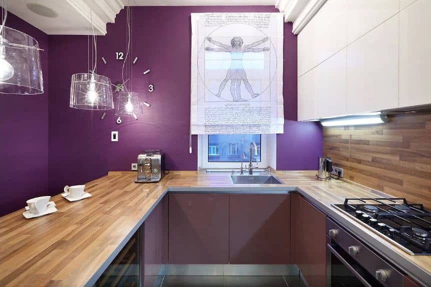 This small kitchen has a U-shaped peninsula to maximize the small space. This peninsula has a wooden countertop that matches with the backsplash of the cooking area. All of these elements are given a nice background of a purple wall adorned with a wall clock and decorative window shade.