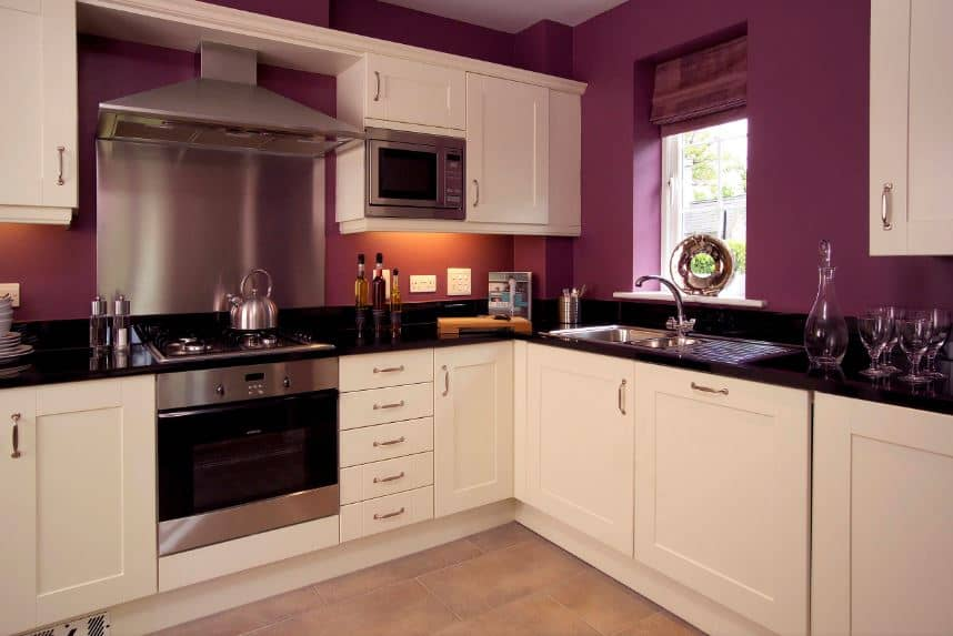 This L-shaped peninsula offers a unique cooking experience with its white cabinetry contrasted by the black countertops and silver appliances. This hue extends to the white floating cabinets that stand out against the deep purple walls.