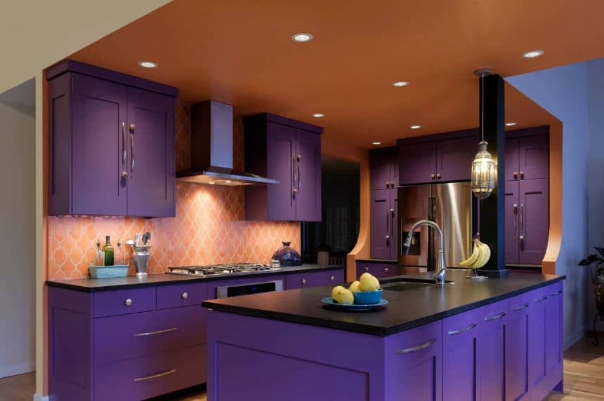 The salmon pink walls and ceiling with recessed lights works well with the purple cabinetry of the island and peninsula with black countertops that make the stainless steel appliances and vent hood stand out.
