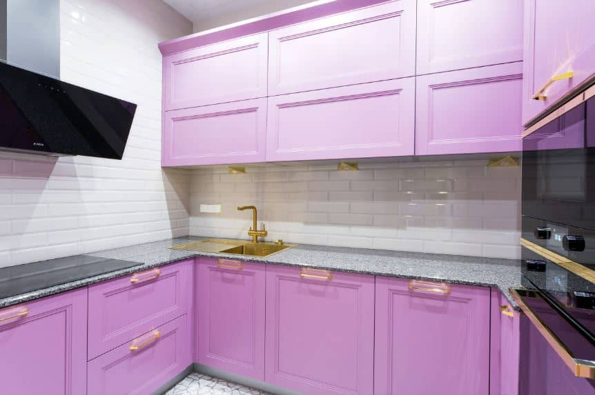 The cheerful pastel purple cabinets and drawers of the L-shaped peninsula is complemented by the bright white tiles of the backsplash that is arranged in a brick wall pattern. This makes the golden faucet stand out that matches with the rest of the kitchen fixtures.