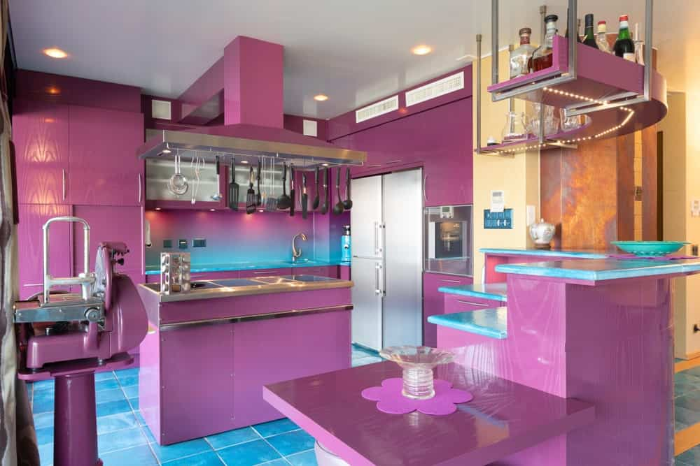 This kitchen is like a fantastical fiction in a dream sequence. It has bright sea green tiles for its flooring and countertops for the peninsulas. This is paired with candy purple structures and walls peppered with a bit of stainless steel appliances.