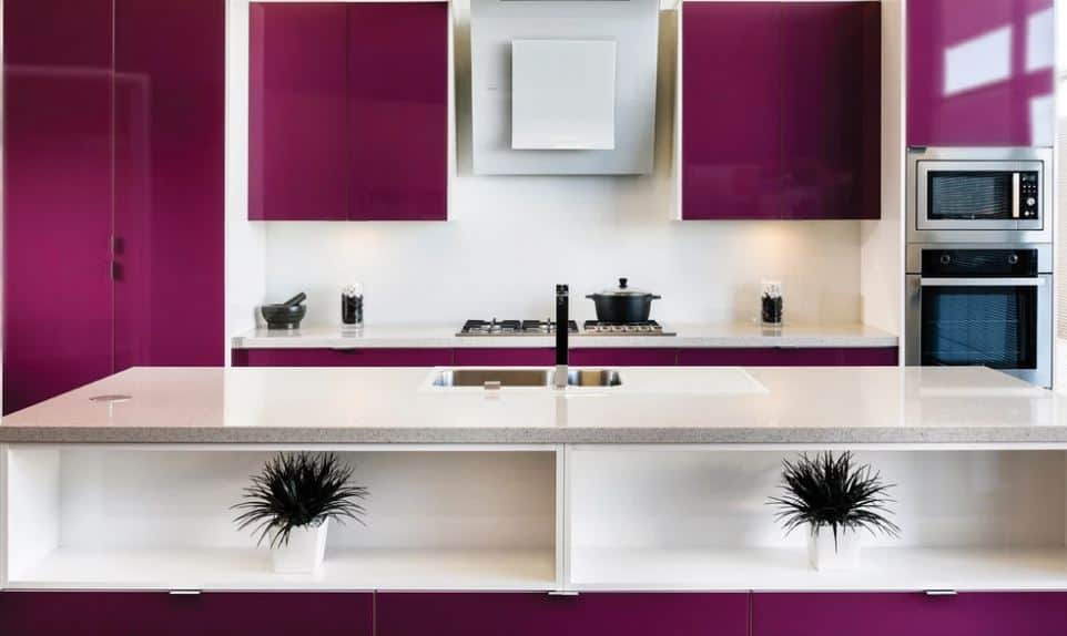 The cooking area of this kitchen has deep purple floating cabinets flanking the vent hood in the middle over the stove-top oven that has a white backsplash that contrasts the purple peninsula. Across from this is the sink area with the same countertop.