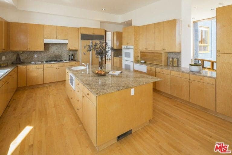 Brown kitchen offers white appliances and wooden cabinetry matching with the breakfast island that blends in with the hardwood flooring. It includes a built-in cooktop along with granite countertops and backsplash.